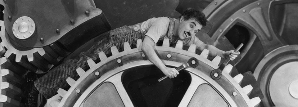 Charlie Chaplin wrenching on a giant cog