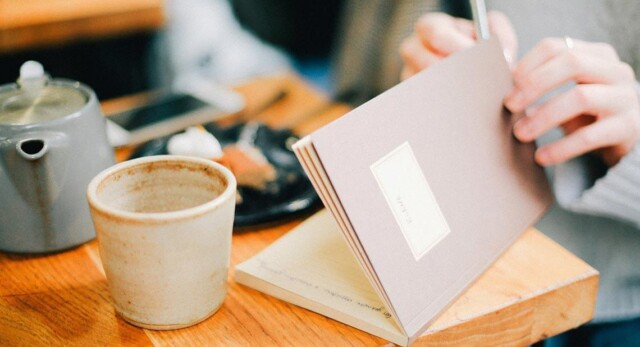 Writing in a journal at a coffee shop