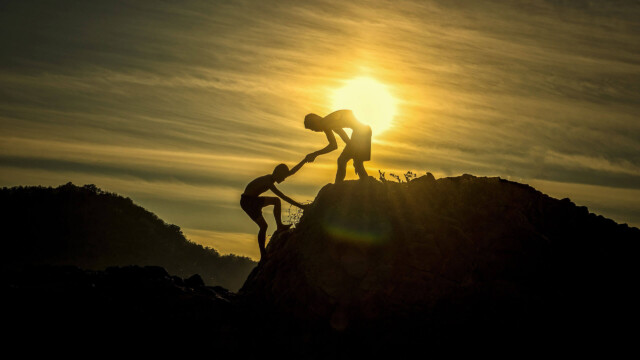 Kids hiking at sunset. One kid is helping the other up a boulder.