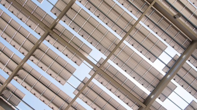Looking up at the sky from underneath a shade structure of solar panels