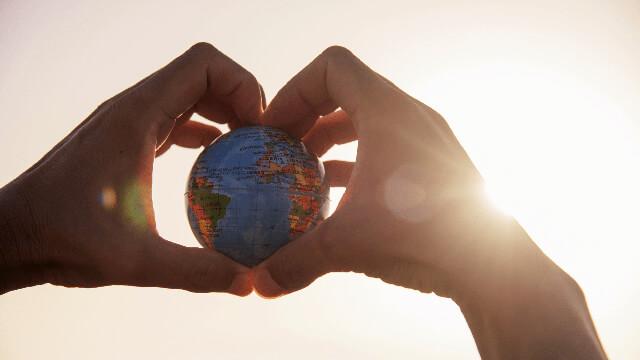 Hands holding up a tiny globe