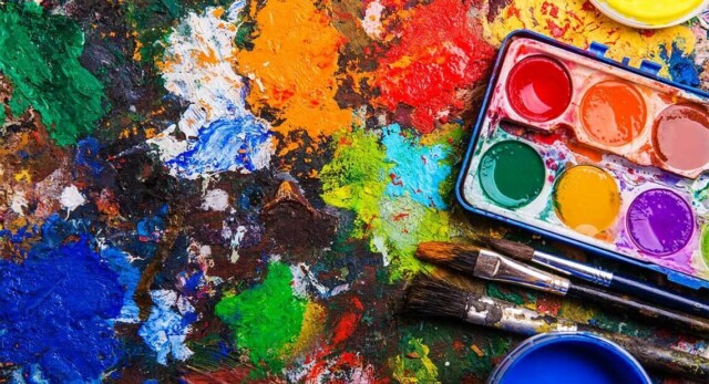 A messy artists palette of paints