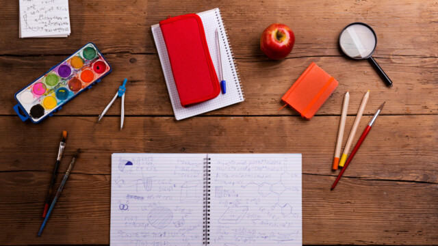 A table with a notebook, pencils and various school supplies.